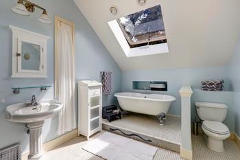 Salle de bain sous les combles avec une fenêtre de toit